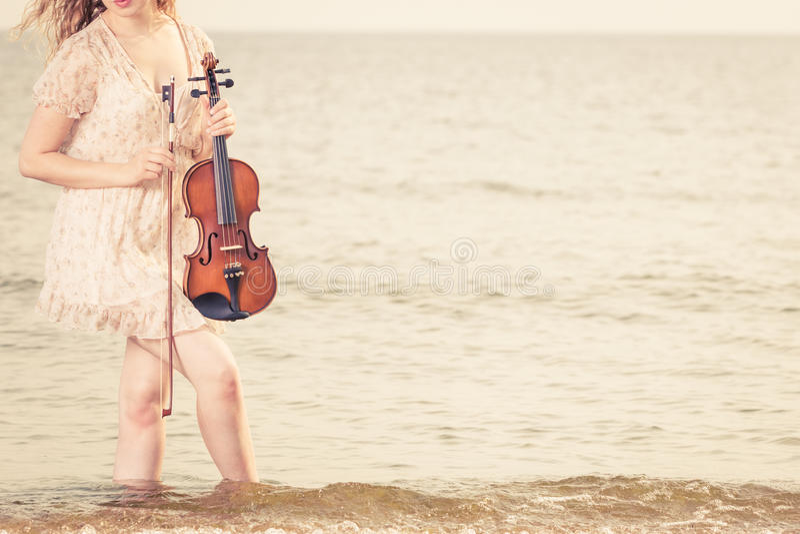 Mujer en la playa cerca del mar que sostiene el violín fotos de archivo