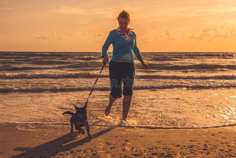 Mujer en la playa con el perro fotografía de archivo libre de regalías