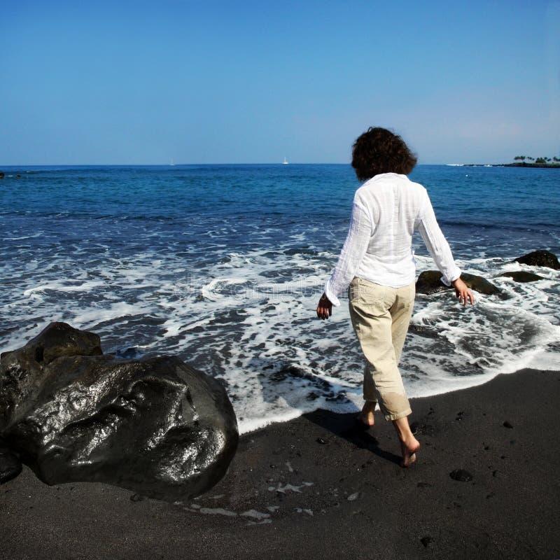 Mujer en la playa negra de la arena foto de archivo libre de regalías