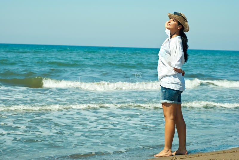 Mujer en la playa que disfruta de rayos del sol foto de archivo