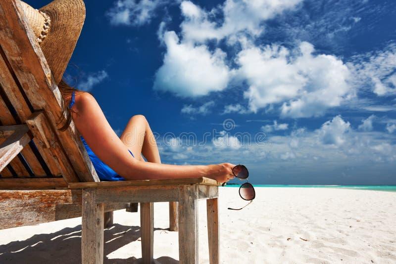Mujer en la playa que sostiene las gafas de sol imagenes de archivo