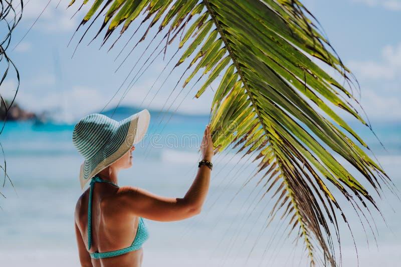 Mujer en la playa que toca la sombra de la hoja de la palmera que lleva el sombrero azul Concepto de lujo de las vacaciones de la fotos de archivo