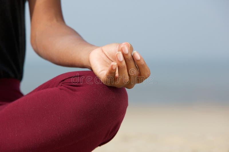 Mujer en la posición de loto en la playa foto de archivo