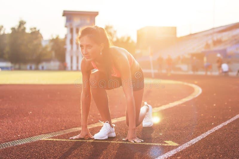 Mujer en la posición de salida lista para correr en estadio foto de archivo