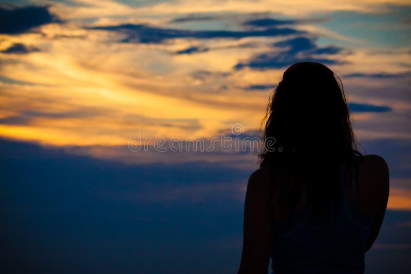 Mujer en la puesta del sol fotografía de archivo libre de regalías