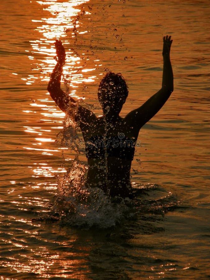 Mujer en la puesta del sol en el mar imágenes de archivo libres de regalías