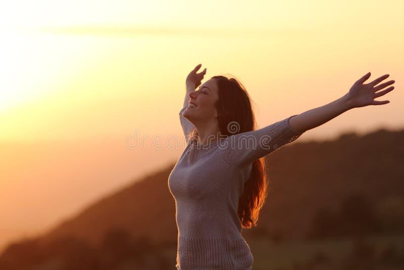 Mujer en la puesta del sol que respira el aire fresco que aumenta los brazos imagen de archivo libre de regalías