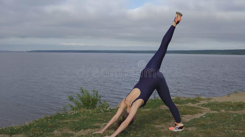 Mujer en la ropa de deportes azul, ejercicio de la yoga al aire libre foto de archivo