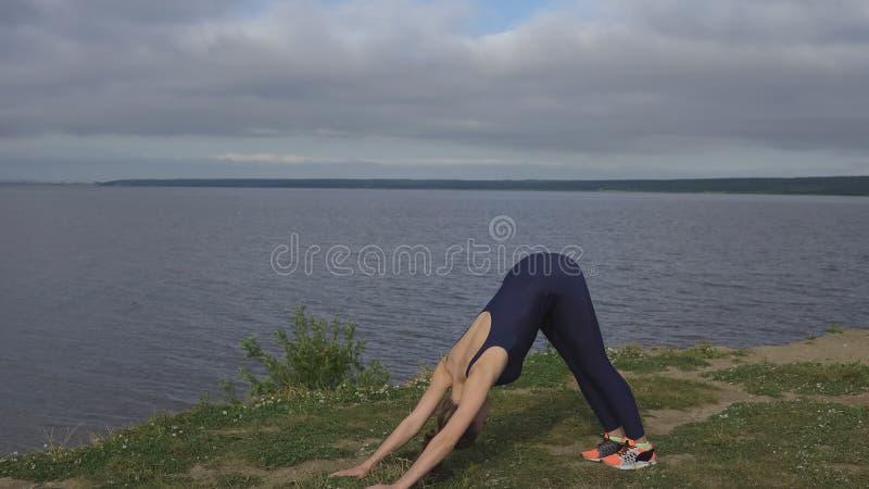Mujer en la ropa de deportes azul que hace las flexiones de brazos, yoga fotos de archivo libres de regalías