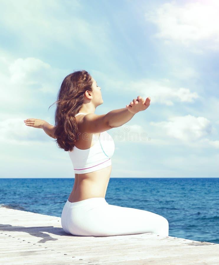 Mujer en la ropa de deportes blanca que hace yoga en un embarcadero de madera Mar y fotos de archivo