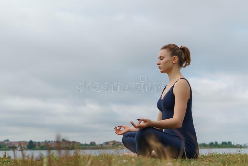 Mujer en la ropa de deportes que se sienta en vista lateral de la actitud de la yoga foto de archivo