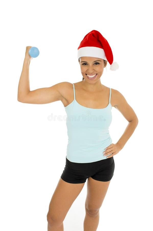 Mujer en la ropa de la aptitud y el sombrero de la Navidad de Papá Noel que llevan a cabo pesas de gimnasia del peso imagen de archivo