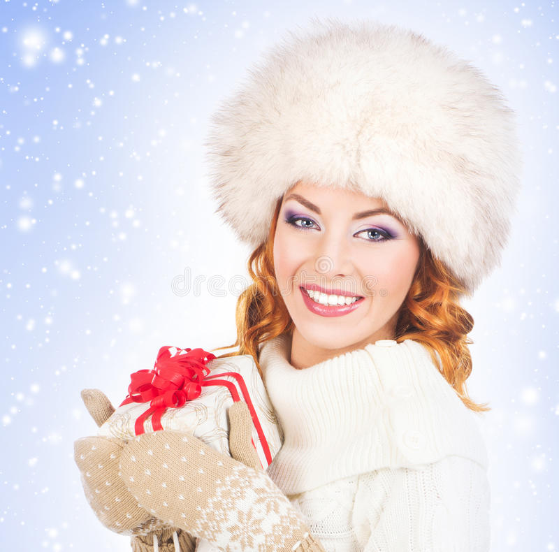 Mujer en la ropa del invierno que lleva a cabo un presente fotografía de archivo libre de regalías