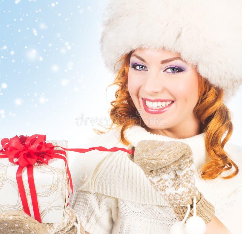 Mujer en la ropa del invierno que lleva a cabo un presente imagen de archivo libre de regalías