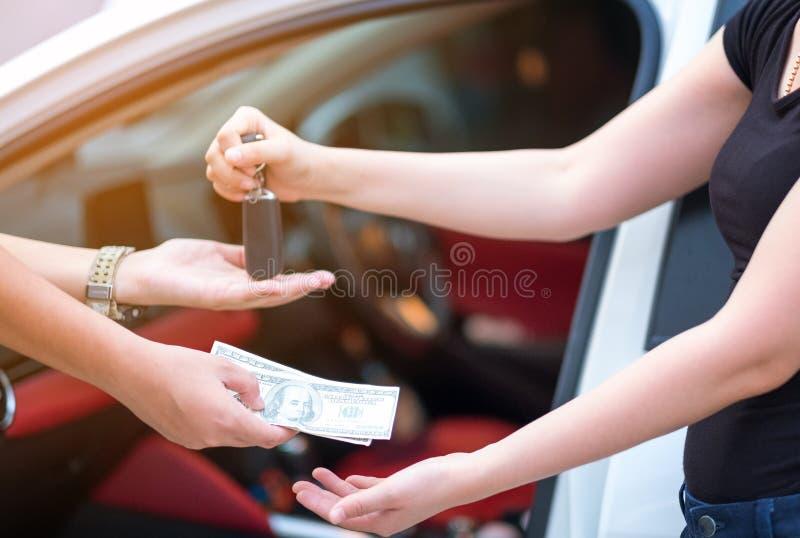 Mujer en la sala de exposición que da el dinero de los dólares y que toma llaves del coche fotos de archivo libres de regalías