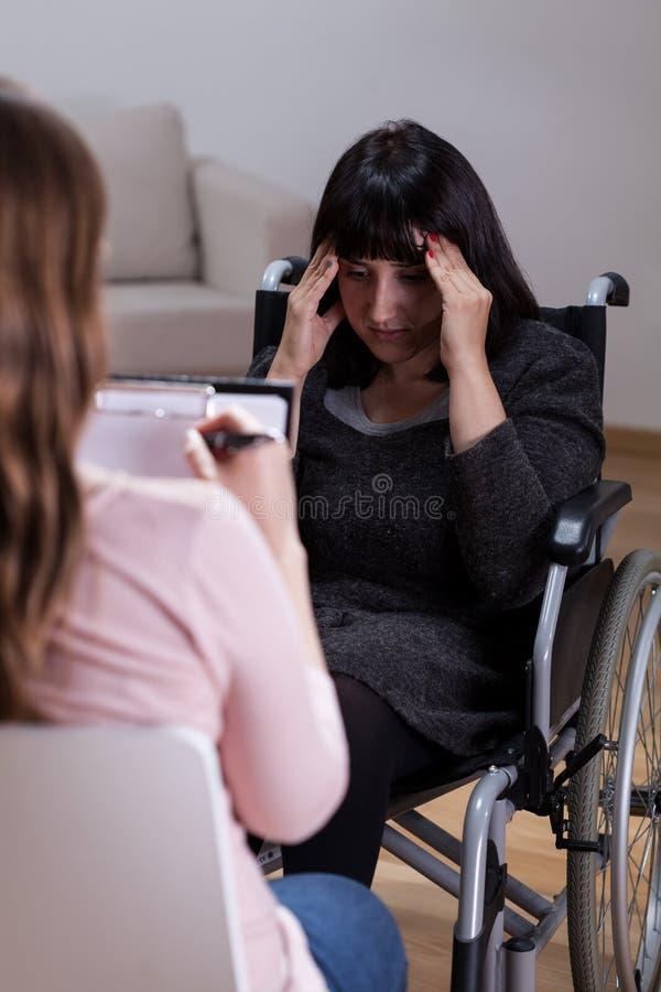 Mujer en la silla de ruedas que habla con el terapeuta imágenes de archivo libres de regalías