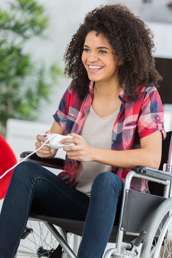 Mujer en la silla de ruedas que juega a los videojuegos en casa foto de archivo libre de regalías