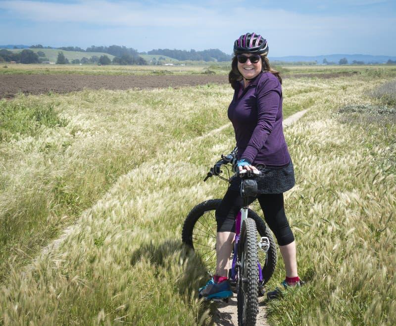 Mujer en la situación púrpura de la camisa con la bici de montaña fotos de archivo