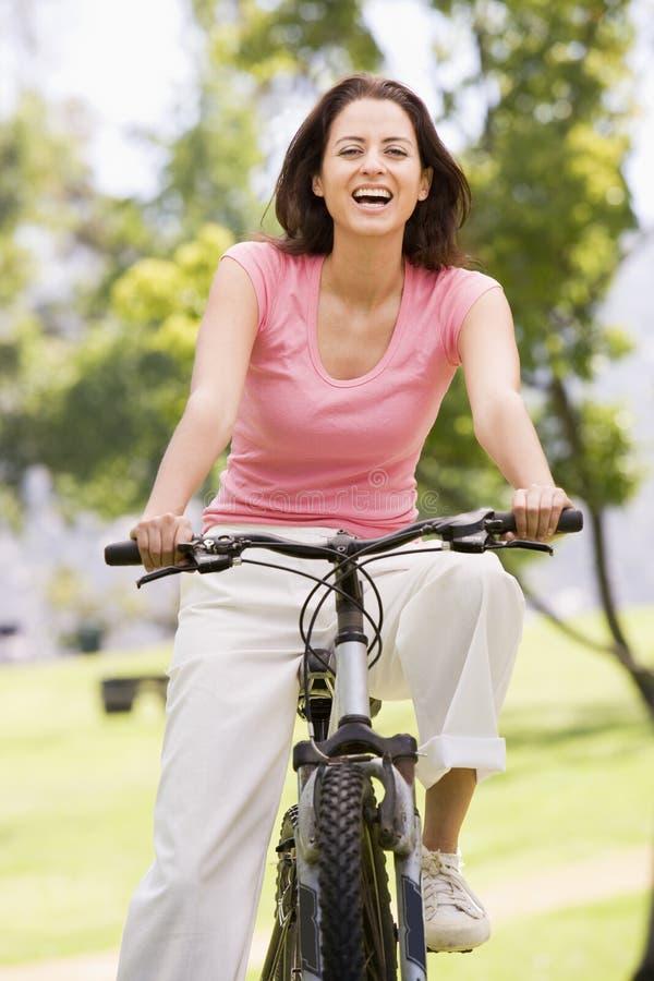 Mujer en la sonrisa de la bicicleta fotografía de archivo libre de regalías