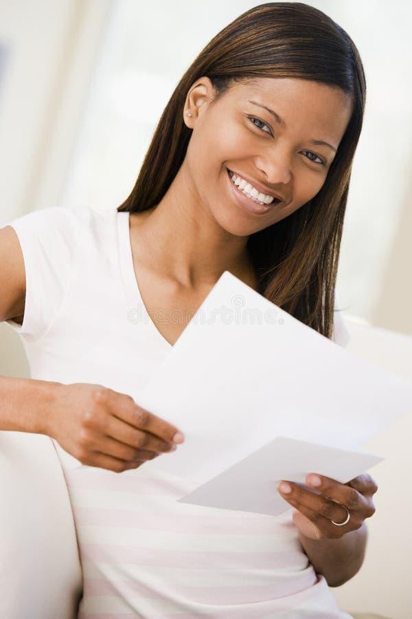 Mujer en la sonrisa de los papeles de la lectura de la sala de estar foto de archivo