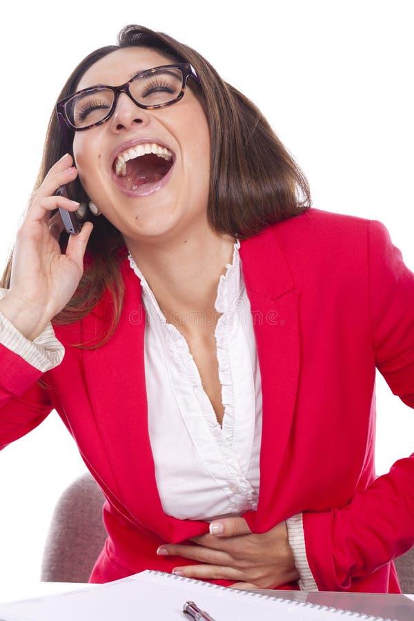 Mujer en la sonrisa del escritorio del trabajo del teléfono imágenes de archivo libres de regalías