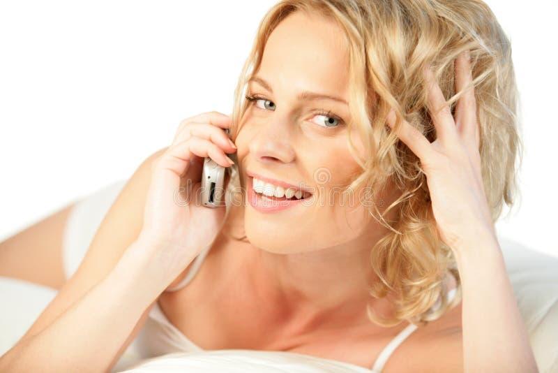 Mujer en la sonrisa del teléfono móvil imagen de archivo