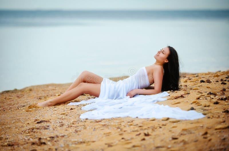 Mujer en la tela blanca en la playa imagen de archivo libre de regalías