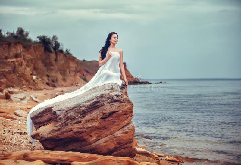 Mujer en la tela blanca en la roca imágenes de archivo libres de regalías