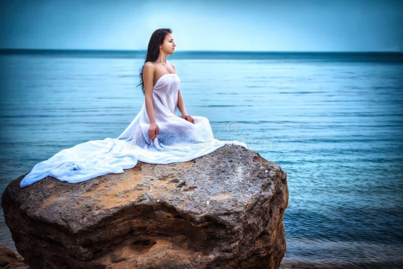 Mujer en la tela blanca en la roca imagen de archivo libre de regalías