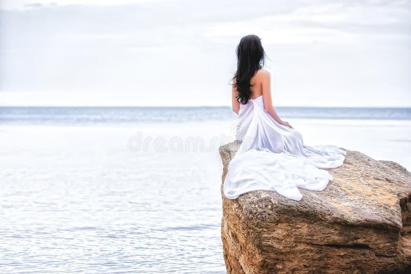 Mujer en la tela blanca en la roca fotografía de archivo libre de regalías