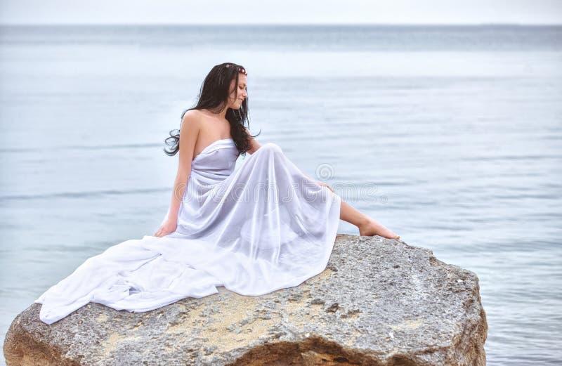 Mujer en la tela blanca en la roca imagen de archivo