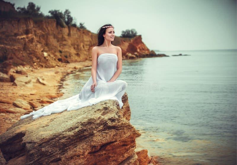 Mujer en la tela blanca en la roca imagenes de archivo