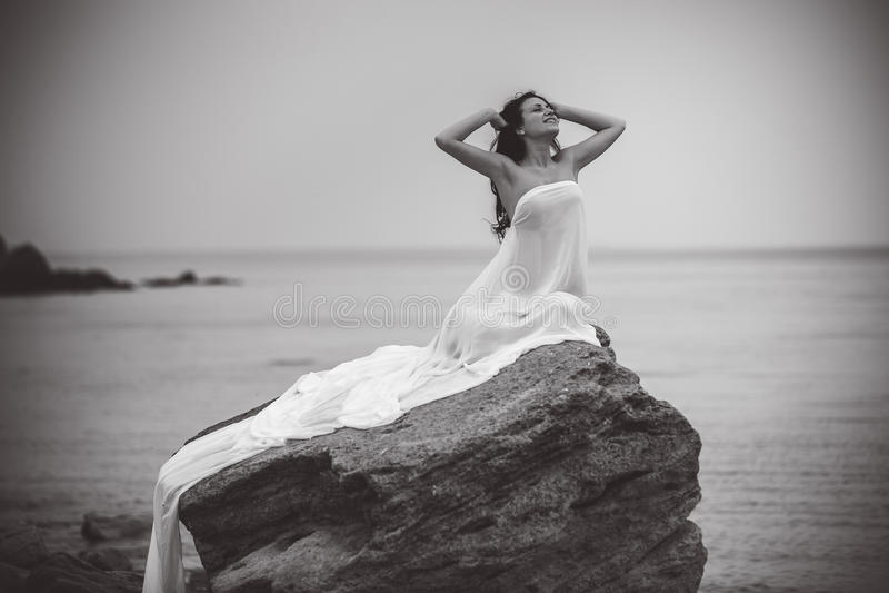 Mujer en la tela blanca en la roca foto de archivo