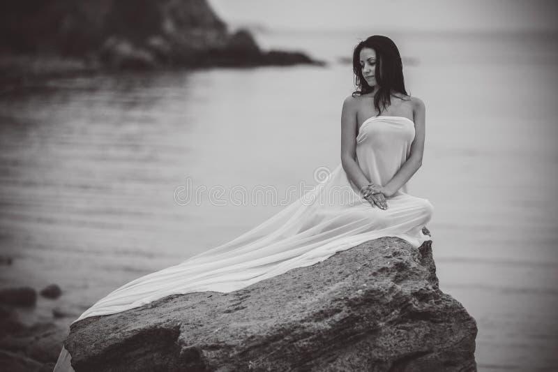 Mujer en la tela blanca en la roca fotos de archivo libres de regalías