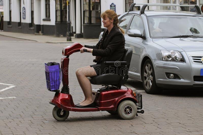 Mujer en la vespa de la movilidad que cruza una calle imagenes de archivo