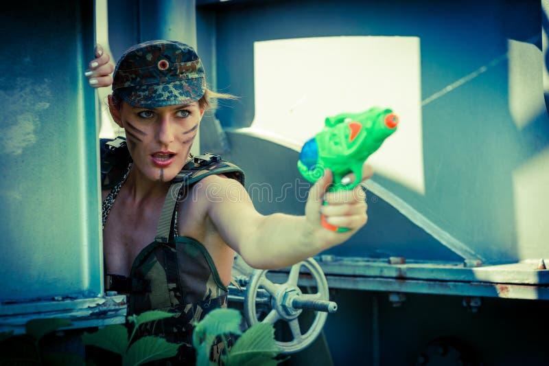 Mujer en lanzamientos del camuflaje de una pistola de agua imagen de archivo