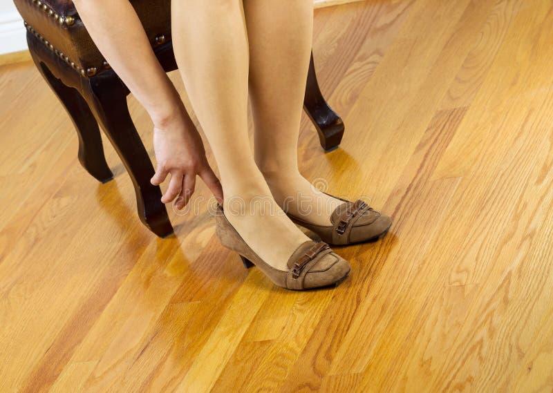 Mujer en las medias que ponen en los zapatos fotografía de archivo