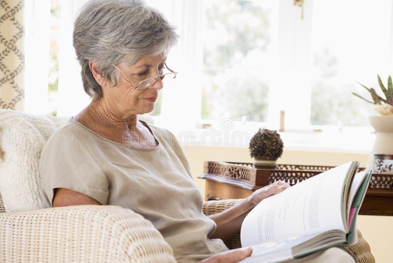 Mujer en libro de lectura de la sala de estar foto de archivo libre de regalías
