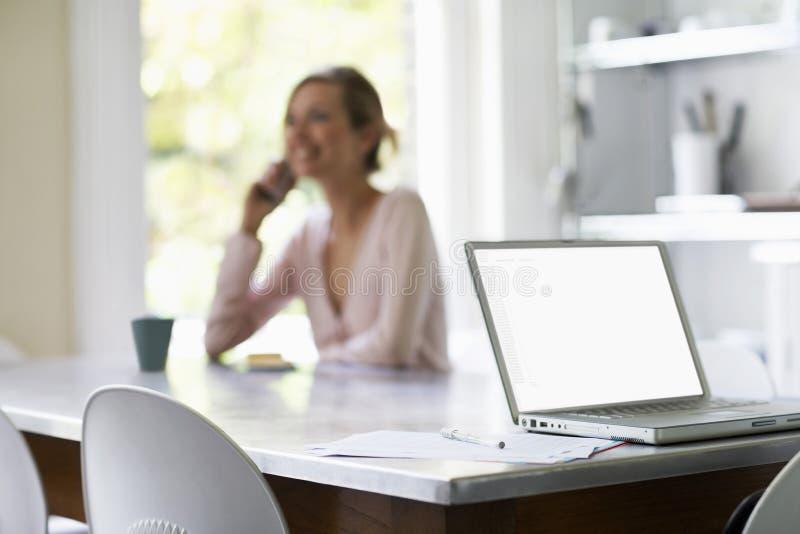 Mujer en llamada con el ordenador portátil y documentos en la tabla fotografía de archivo libre de regalías