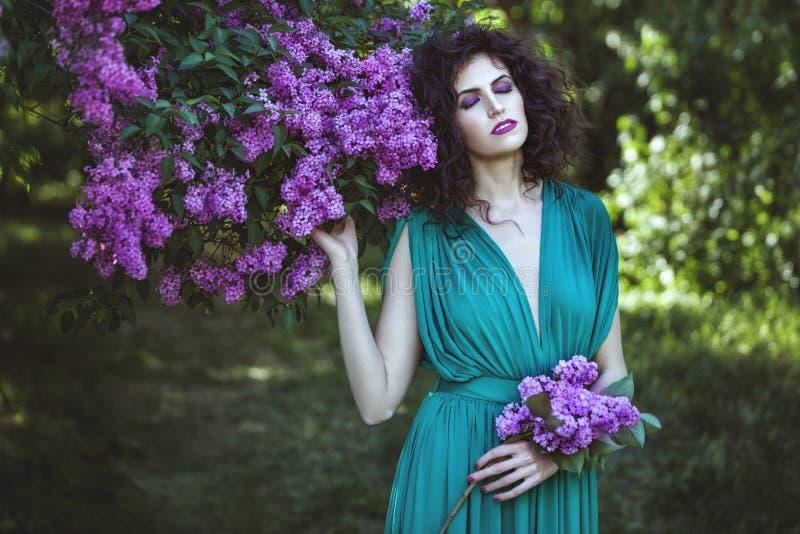 Mujer en los arbustos de la lila fotos de archivo