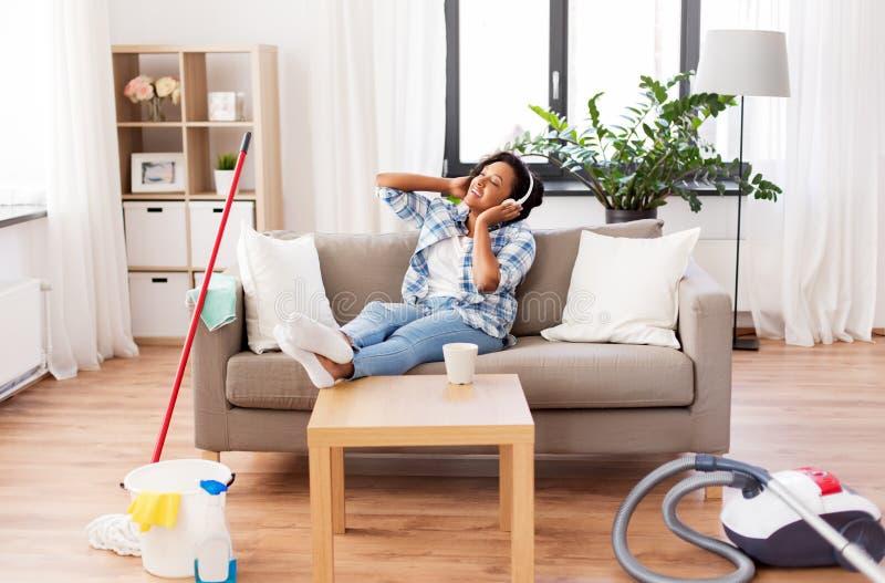 Mujer en los auriculares que descansan despu?s de la limpieza casera imagen de archivo