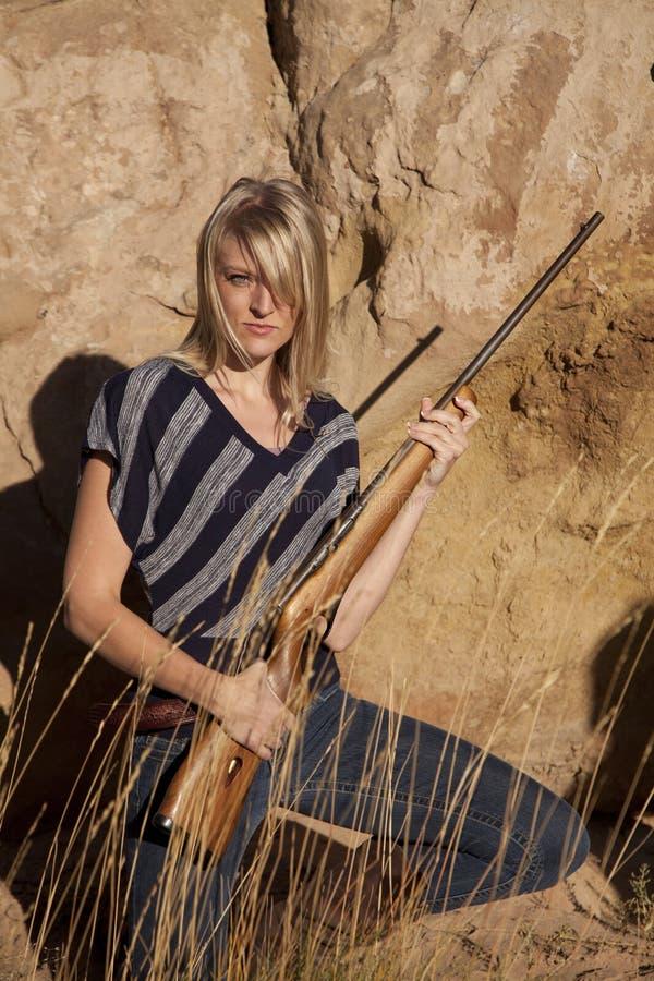 Mujer en los gras que sostienen el arma imágenes de archivo libres de regalías