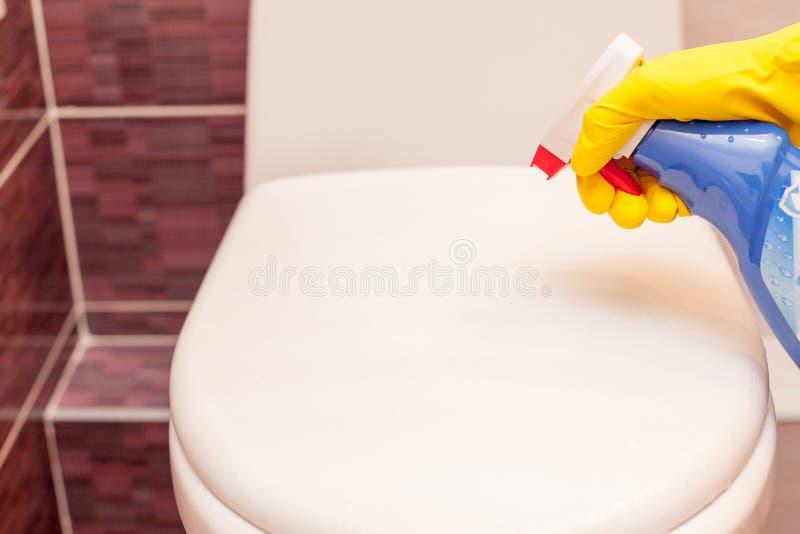 Mujer en los guantes de goma amarillos que limpian la cubierta de asiento de inodoro con el paño y el detergente anaranjados imágenes de archivo libres de regalías