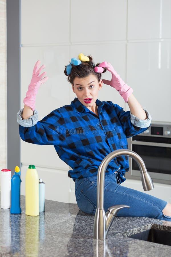 Mujer EN los guantes de una limpieza que se sientan en un worktop de la cocina foto de archivo libre de regalías