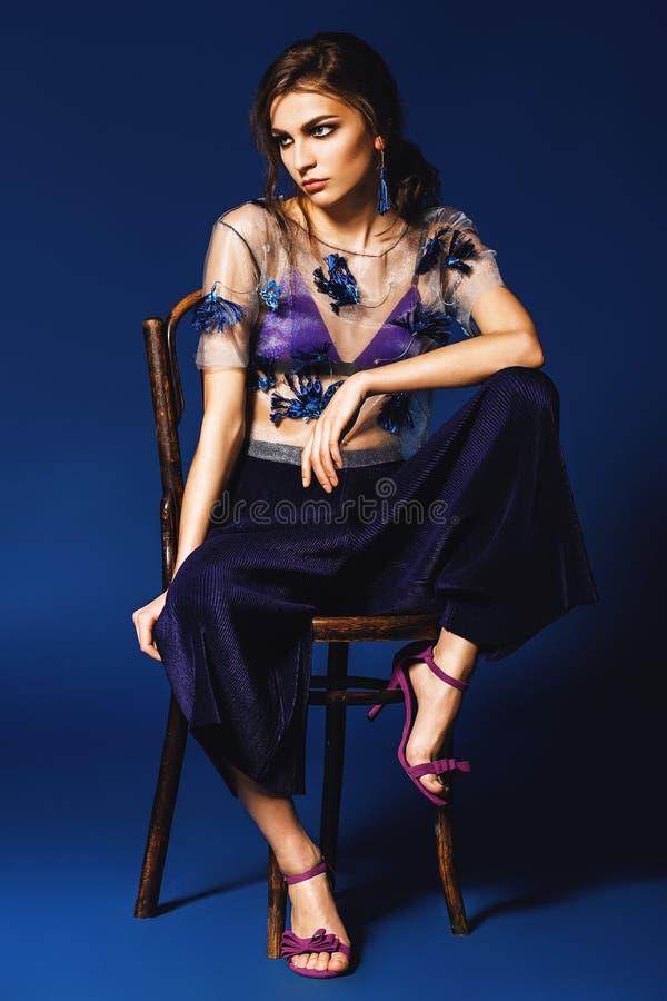 Mujer en los pantalones y el top transparente floral que se sientan en chai de madera foto de archivo libre de regalías