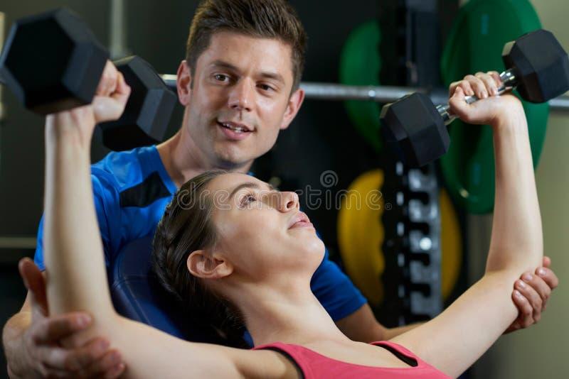 Mujer en los pesos de elevación del gimnasio alentadores por el instructor personal foto de archivo