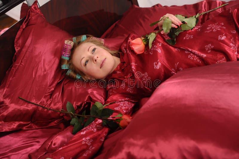 Mujer en los pijamas rojos que mienten en una cama en el lino rojo de seda con bigudíes de pelo y una rosa en su mano fotos de archivo