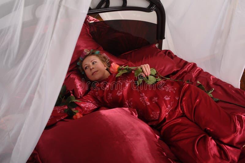 Mujer en los pijamas rojos que mienten en una cama en el lino rojo de seda con bigud?es de pelo y una rosa en su mano fotos de archivo libres de regalías