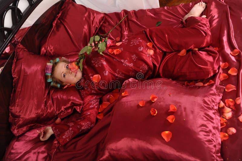 Mujer en los pijamas rojos que mienten en una cama en el lino rojo de seda con bigud?es de pelo y una rosa en su mano imagen de archivo