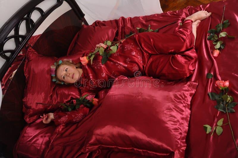 Mujer en los pijamas rojos que mienten en una cama en el lino rojo de seda con bigud?es de pelo y una rosa en su mano imagen de archivo libre de regalías